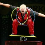 1280px-Rola_bola_man_with_neck_and_thigh_in_tight_hoop